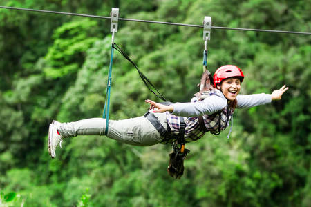 adult tourist wearing casul clothing on zip line trip, selective focus against blured forest 스톡 콘텐츠