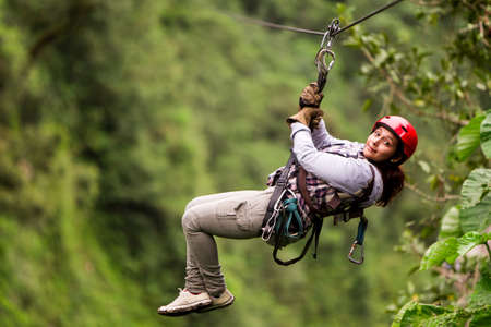gliding: adult tourist wearing casul clothing on zip line trip, selective focus against blured forest Stock Photo