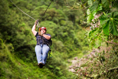 oversized adult man on zip line or canopy trip, nearby of banos de agua santa, ecuador Stock Photo
