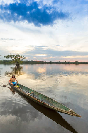 tribal park: Indigenous adult man with canoe on lagoon Grande, Cuyabeno national park, Ecuador at sunset, model released