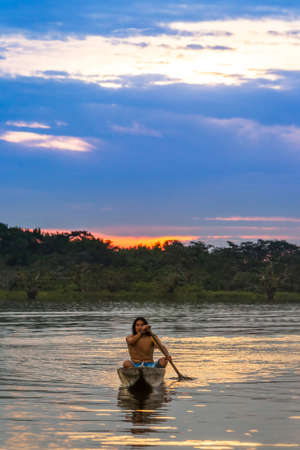 watershed: Indigenous adult man with canoe on lagoon Grande, Cuyabeno national park, Ecuador at sunset, model released