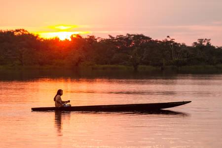 ラグーン グランデ、Cuyabeno 国立公園、夕日、モデル リリースにエクアドルでカヌーと先住民族の成人男性