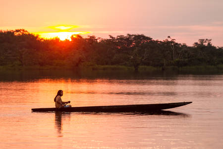 Indigenous adult man with canoe on lagoon Grande, Cuyabeno national park, Ecuador at sunset, model released