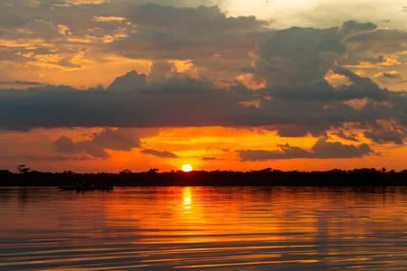 medium shot: Orange sky on lagoon Grande, Cuyabeno National Park Ecuador, polarized medium shot on sunset Stock Photo
