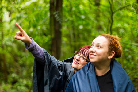 adventurers: Group of two adult tourist woman into the jungle pointing to left upper corner Stock Photo