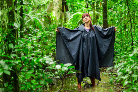 adventurers: Tourist woman into Amazonian jungle showing of typical equipment and clothing for this enviorement, rain poncho and rubber boots