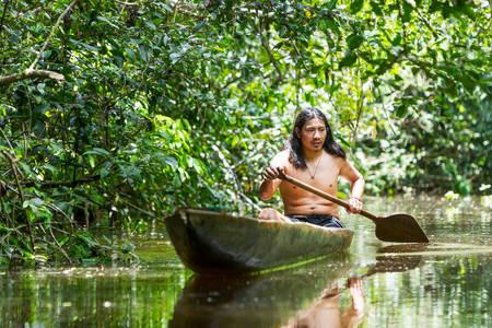 indio americano: Hombre adulto Indígena sobre canoa de madera típico choped de un solo árbol de navegación turbias aguas de Ecuador selva amazónica primaria Foto de archivo