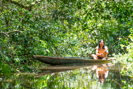 american culture: Indigenous adult man on typical wooden canoe choped from a single tree navigating murky waters of Ecuadorian Amazonian primary jungle