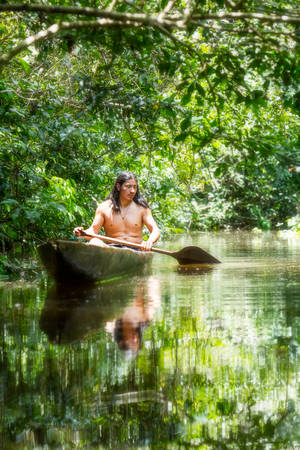 navigating: Indigenous adult man on typical wooden canoe choped from a single tree navigating murky waters of Ecuadorian Amazonian primary jungle