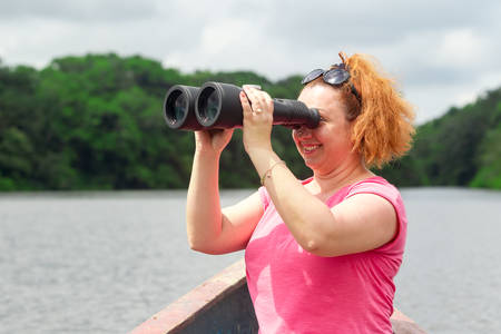 amazonian: Tourist woman with high power binoculars in Amazonian jungle against dense vegetation Stock Photo