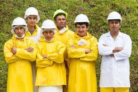 sadism: Team of slaughterhouse workers or butchers and veterinary doctor wearing protection equipment posing for a group photo