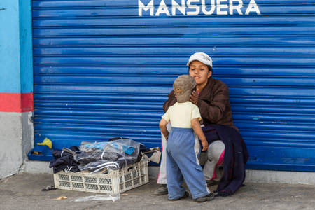 living moment: Salasaca, Ecuador - 24 January 2014: Emotional Moment With A Street Seller Woman Giving Attention To Her Young Son In Salasaca On January 24, 2014