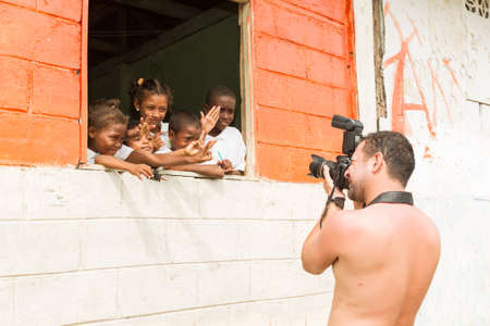 opportunist: Santa Rosa, Ecuador - 26 July 2015: Photographer Taking A Picture Of A Group Of Afro American Children On The School Window In Santa Rosa On July 26, 2015 Editorial