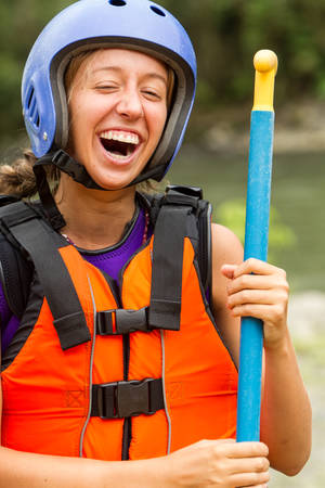 white water: Portrait Of Young Lady Laughing White Water Rafting Equipment Stock Photo