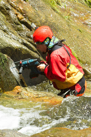 'rock drill': Instructor Drilling Holes For A New Canyoning Route In Chama Waterfall Ecuador