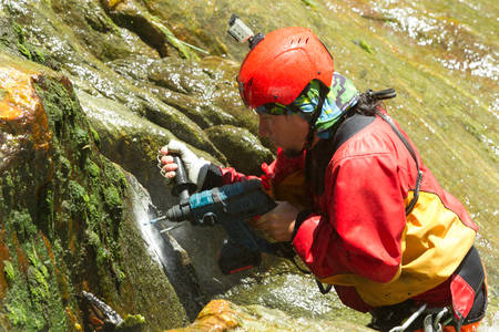 fun at work: Instructor Drilling Holes For A New Canyoning Route In Chama Waterfall Ecuador