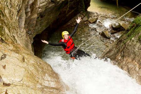 descending: Adult Woman Wearing Waterproof Equipment Descending A Waterfall