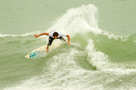 water wave: Young Man Surfing On A Balsa Surfboard