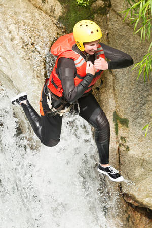 extreme angle: Young Woman Wearing Wetsuit Helmet And Life Jacket Jumping Into A Waterfall