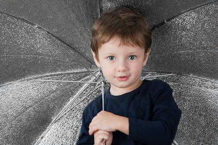 reflector: Little Child Posing As Photo Assistant Holding A Reflector Umbrella Stock Photo