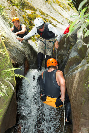 rappel: Group Of Two Adult Men With A Professional Guide On Canyoning Expedition In South America