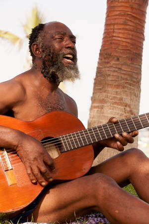 look latino: Old Black Men Playing Guitar On A Tropical Island Stock Photo
