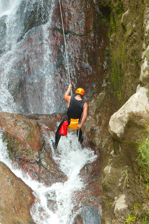 rappelling: Canyoning On Pucayacu Waterfall Canyon Near Banos Ecuador Stock Photo