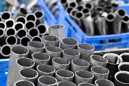exhaust system: Gray Stainless Pipes Stacked In Storage Boxes They Are Used In Automotive Industry For The Exhaust System Stock Photo