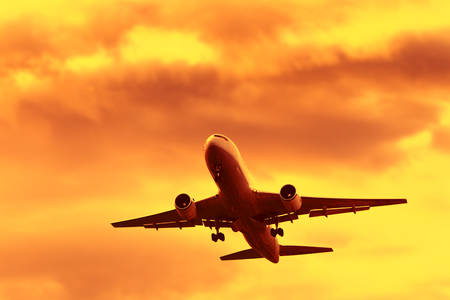 flight: Jet Airplane In Flight At Sunset Time Stock Photo
