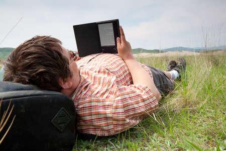 personas leyendo: Individuo que pone en la hierba y leyendo un libro Foto de archivo