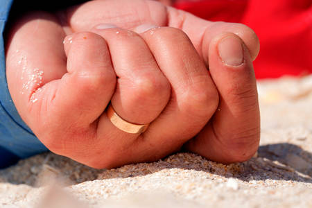 close up of a married man resting on the beach