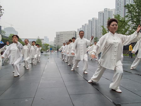 categorized: CHENGDU, CHINA - JUNE 4, 2012: Unidentified people practicing tai chi on the street of Chengdu, China. In China, tai chi  is categorized under the Wudang grouping of Chinese martial arts,  applied with internal power.