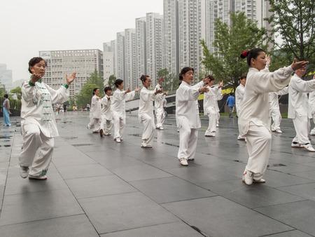 artes marciales: CHENGDU, CHINA - 04 de junio 2012: La gente no identificada que practican tai chi en la calle de Chengdu, China. En China, el tai chi se clasifica bajo la agrupaci�n de Wudang de las artes marciales chinas, aplicado con el poder interno.
