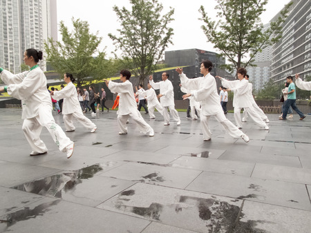 grouping: CHENGDU, CHINA - JUNE 4, 2012: Unidentified people practicing tai chi on the street of Chengdu, China. In China, tai chi  is categorized under the Wudang grouping of Chinese martial arts,  applied with internal power.