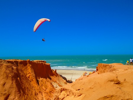 parapente: FORTALEZA, BRAZIL - OCTOBER 12, 2015: Unidentified people and paragliders at the Canoa Quebrada Beach. It was a Swiss pilot who introduced this new practice: Gerome Bertand Saunier, best known as Jeronimo Editorial