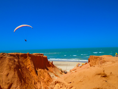 FORTALEZA, BRAZIL - OCTOBER 12, 2015: Unidentified people and paragliders at the Canoa Quebrada Beach. It was a Swiss pilot who introduced this new practice: Gerome Bertand Saunier, best known as Jeronimo Editorial