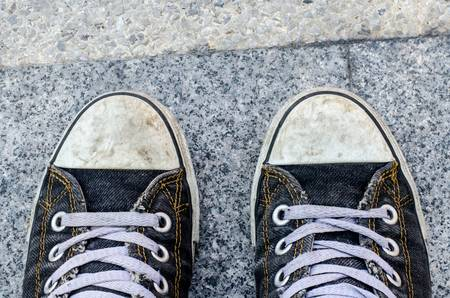 blue dirty Sneakers on street on free day Stock Photo
