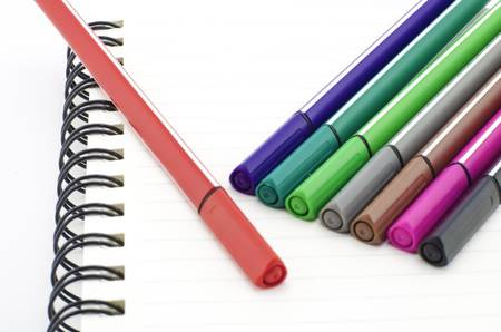 colorful pen with notebook isolated on white background photo