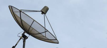 Satellite dish on blue sky background photo