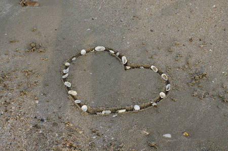 drawing heart on the sand in the beach photo