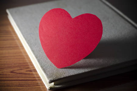 diary of love with notebook and heart on wood background photo