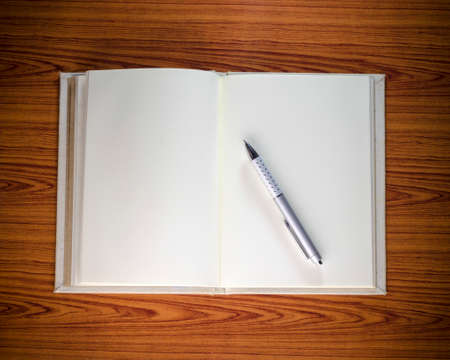 notebook with pen on wood background photo