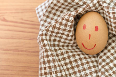 smile love egg couple in brown kitchen towel on wood table