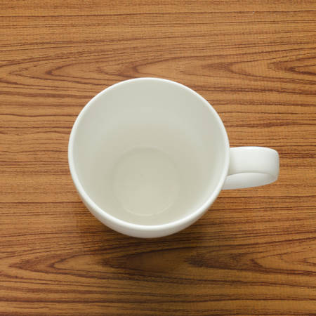 empty coffee cup on brown kitchen towel and wood table Stock Photo