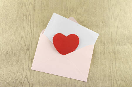 red heart with pink envelope on wooden background photo