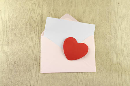 red heart with pink envelope on wooden background