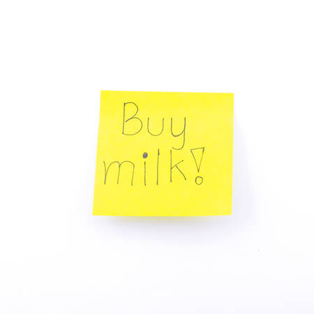 yellow notepad: buy milk text on yellow note isolated on white background Stock Photo