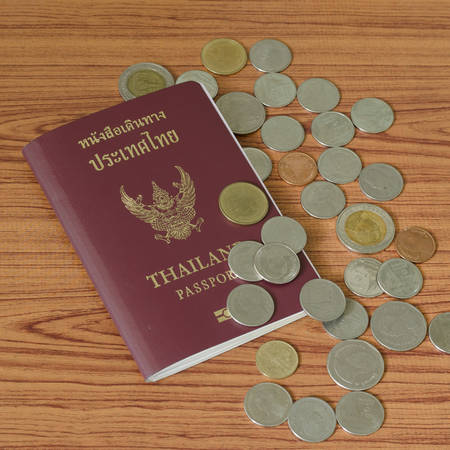 thai passport with coin on wood table background photo