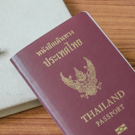thai passport with notebook on wood table background photo