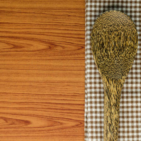 brown kitchen towel with spoon on wood background photo